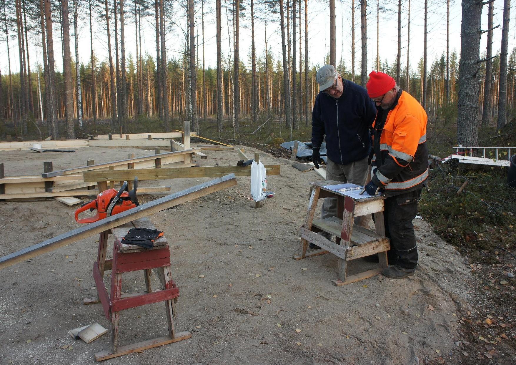Yhdistyksen varapuheenjohtaja Lasse Nirhamo ja vastaava työnjohtaja Matti Kilpeläinen tutkivat kodan rakennuspiirustuksia 16.10.2014.
