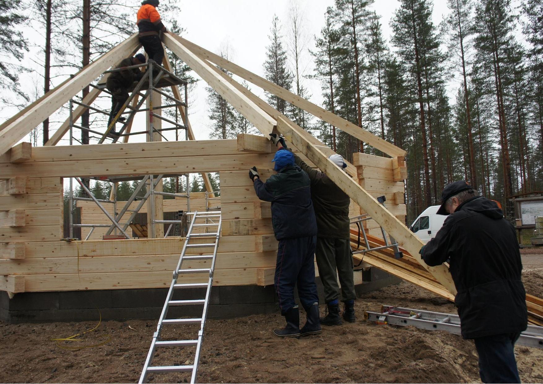 Viimeinen kattotuoli nousee paikoilleen ja kota on harjassa. Matti Kilpeläinen ja Tuomo Martikainen telineillä ja alhaalla Hannu Huuskonen, Tauno Oksanen ja Sulo Eskelinen.