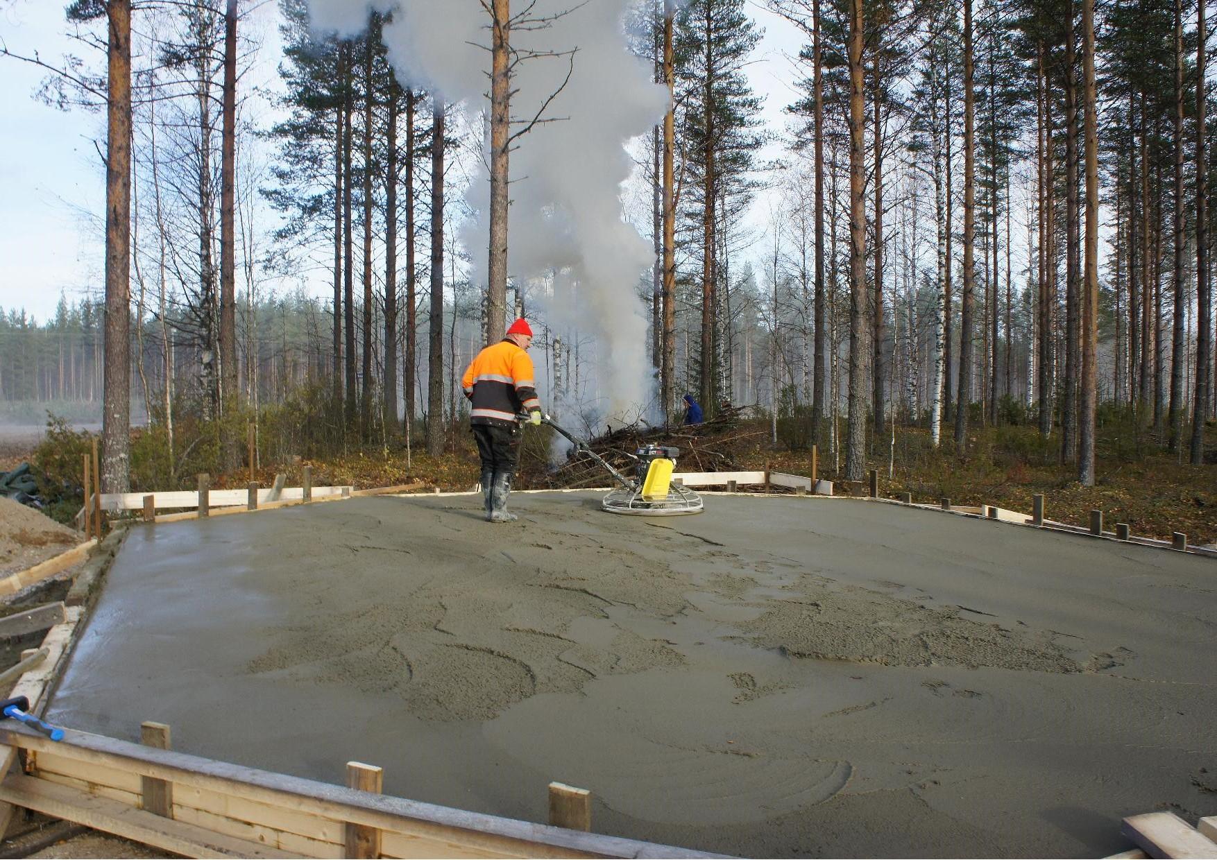 Matti Kilpeläinen tasoittamassa pohjan betonia hiertimellä.