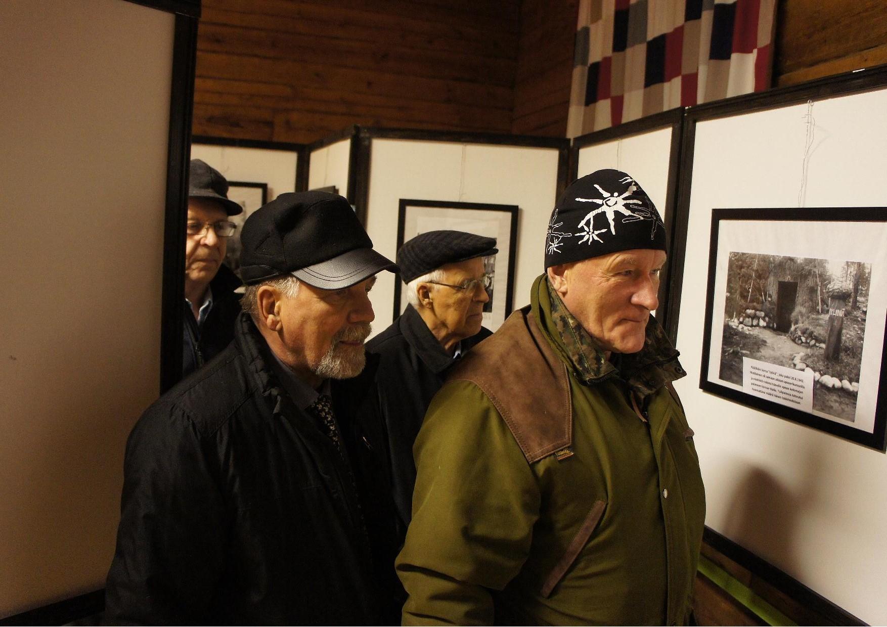 Valokuvanäyttelyyn tutustumassa kyläseuran puheenjolhtaja Heikki Turunen takana veteraani Olavi Tiittanen sekä Tauno Oksanen.