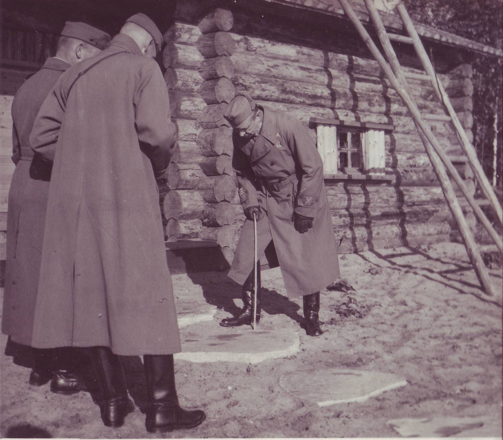 Mannerheim Rukajärvellä 1942 tutkimassa saunan rappukiven kaunista koristetta - saniaiskuviota.