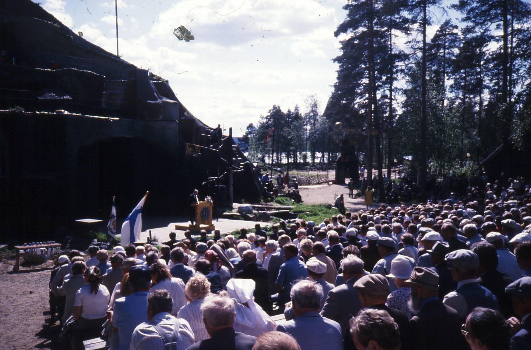 Perustajajäsenemme Pentti Perttuli valittiin tällä paikalla Nurmeksessa 15.6.1986 Rukajärven suunnan historiikkitoimikunnan jäseneksi. Hän pitää kuvassa n. 3000 juhlaan kokoontuneelle veteraaniveljelleen juhlapuhetta. Nyt Yhdistys palasi pitämään seminaaria tälle samalle paikalle.