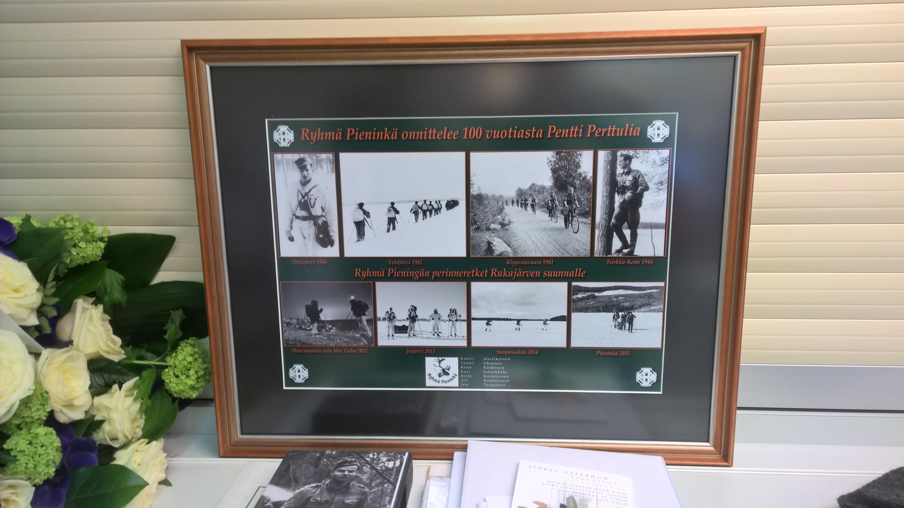 Ryhmä Pieningän onnittelut, kuvakooste, jossa yhtyvät Pentti Perttulin ja ryhmän yhteiset ladut Muurmannin radalle ja Pieningän saloille. Taulun luovutti rajakapteeni Tauno Oksanen.
