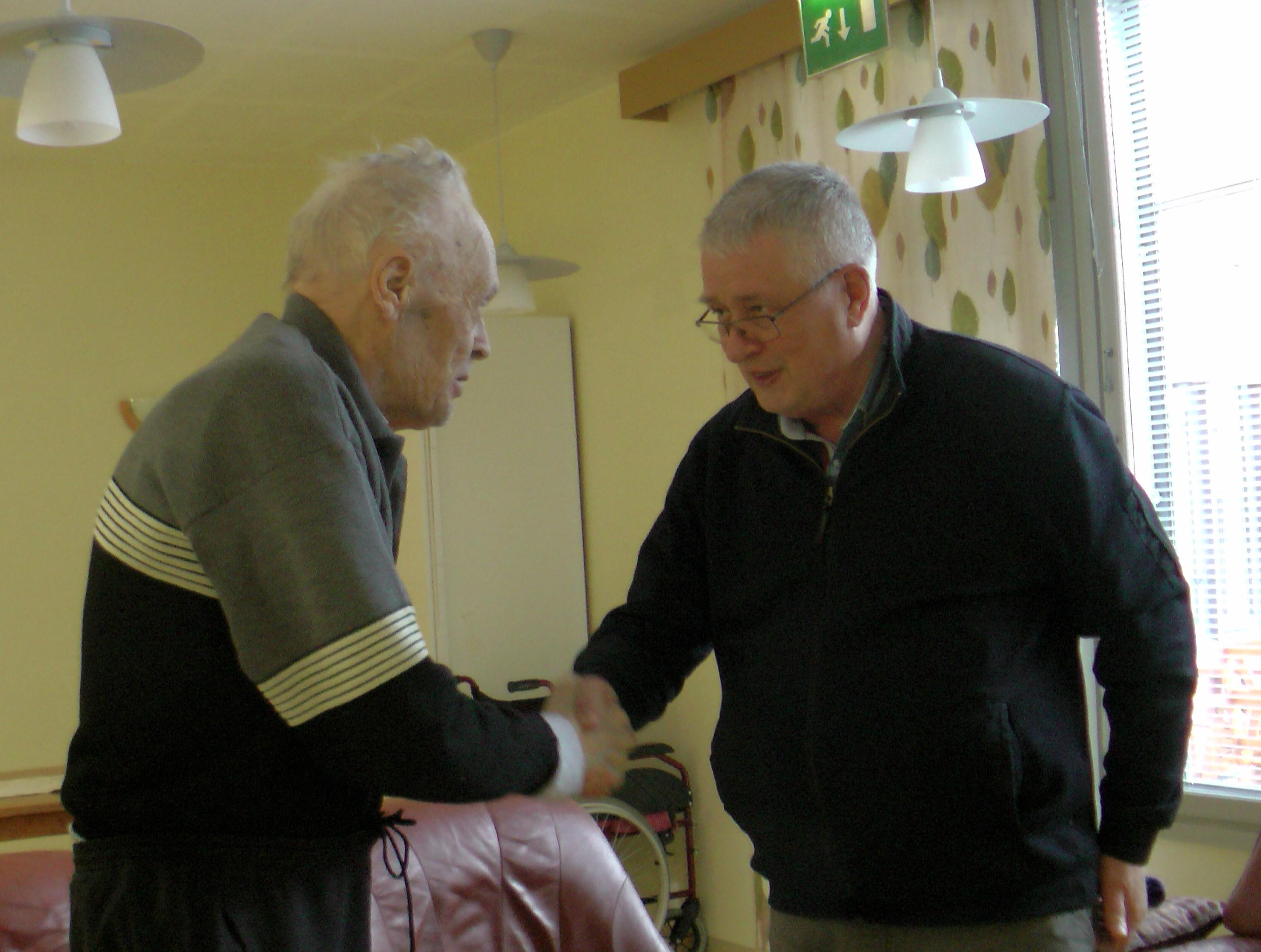 RSHYry:n hallituksen jäsen Seppo Räihä onnittelee 90-vuotiasta veteraania filosofian lisensiaatti, rovasti Erkki Kaikkosta. Kuvat Antero Huttunen ja Tenho Tikkanen, jotka olivat myös onnittelukäynnillä.