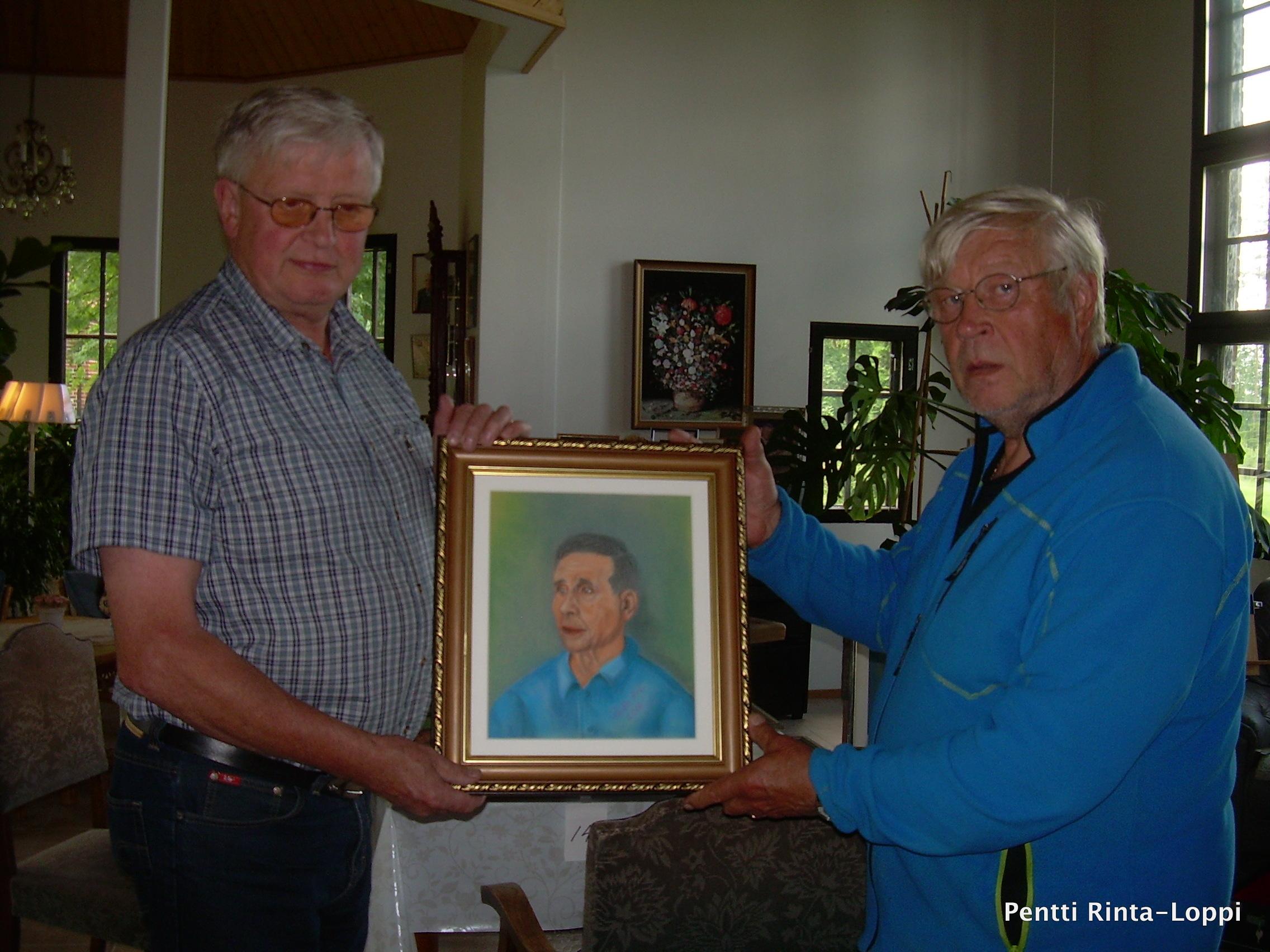 Pentti Taivalmäki otti vastaan Pentti Rinta-Lopin Väinö Taivalmäen muotokuvamaalauksen.
