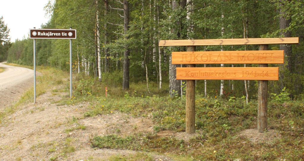 Jukolan motiksi kutsutun koulutuskeskuksen paikalle pystytetty opaskyltti. Kuvassa näkyy myös kyltti, jollaisilla Rukajärven tie on merkitty Suomen puolella.