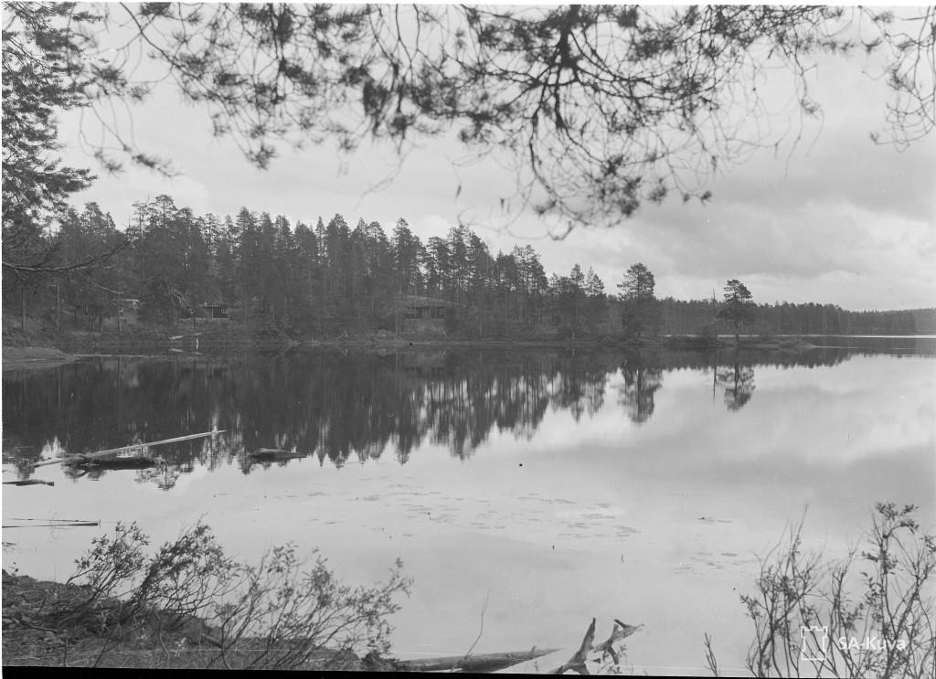 Komentajan Rukapirtti niemen kärjessä Novinkajärven rannalla, sauna niemen takana ja Ahman komentopaikka aja esikunta siitä vasemmalle.