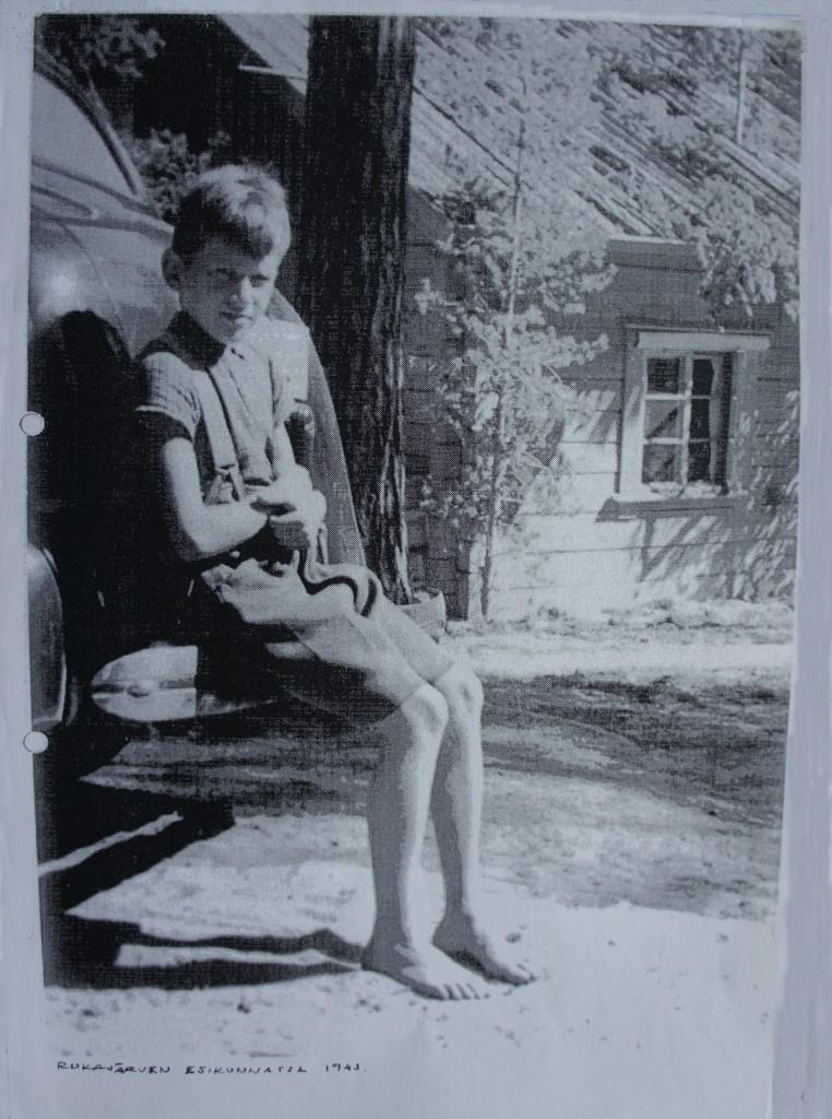 Erkki Simo Susi 9-vuotiaana Rukajärven suunnan joukkojen esikunnassa, istuu Raappan käytössä olleen Buik-merkkisen auton puskurilla 1943 kesäkuussa. Isällä oli Backard-merkkinen auto.Takana Sulo V. Suden  komentokorsu, joka osin muutettuna on edelleen paikallaan, nyt vuorattu, punaiseksi maalattu ja kuistilla laajennettuna. Kuva Erkki Suden arkisto.