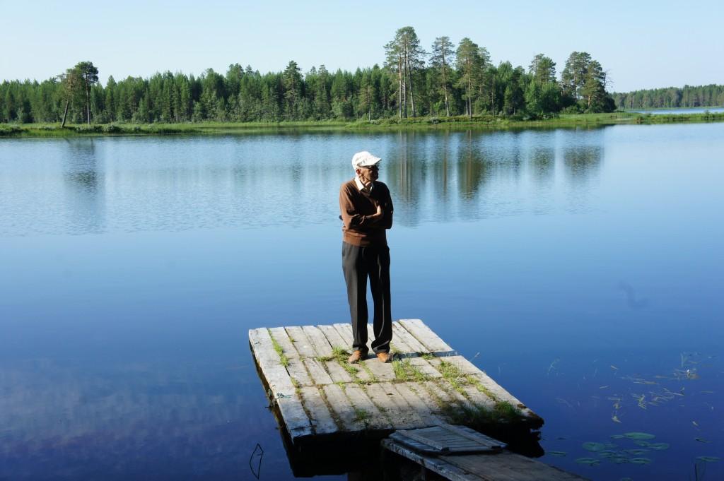 """Nostalgisin valokuva Erkki Simo Suden heinäkuiselta (4 – 5.7.2013) matkalta otettiin Rukajärven rintaman joukkojen esikunnan, komentaja Raappanan ja hänen isänsä Sulo V. Suden komentopaikan rannassa. Tässä maisemassa hän vietti Jatkosodan aikaiset kesänsä vuosina 1943 – 44. Tykkitulen kumu kuului kaukaisena jatkuvasti. Täällä palaa tunteikkaat muistot tuoreina mieliin. Täällä hän kuulee komentajansa ystävällisen puhuttelun, isänsä suorasukaisemmat saksalaistyyliset komennot ja Raappanan karhunpentujen erityisesti """"Mesikan"""" hunajan maiskuttelun –näm..mäm..näm…vieläkin elävinä."""