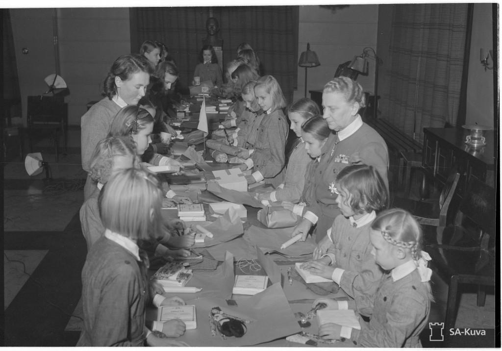 Pikkulotat valmistavat joulupaketteja rintamamiehille lottapäällikkö Fanni Luukkosen läsnäollessa. Laivanvarustajank. 6. 1943.11.20. SA-kuva.