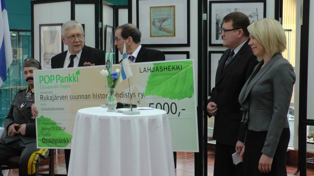 Osuuspankki Poppian toimitusjohtaja Timo Niskanen ja markkinointipäällikkö Sari Kiiskinen luovuttivat historiayhdistyksen edustajille huomattavan 5.000 €:n lahjashekin.