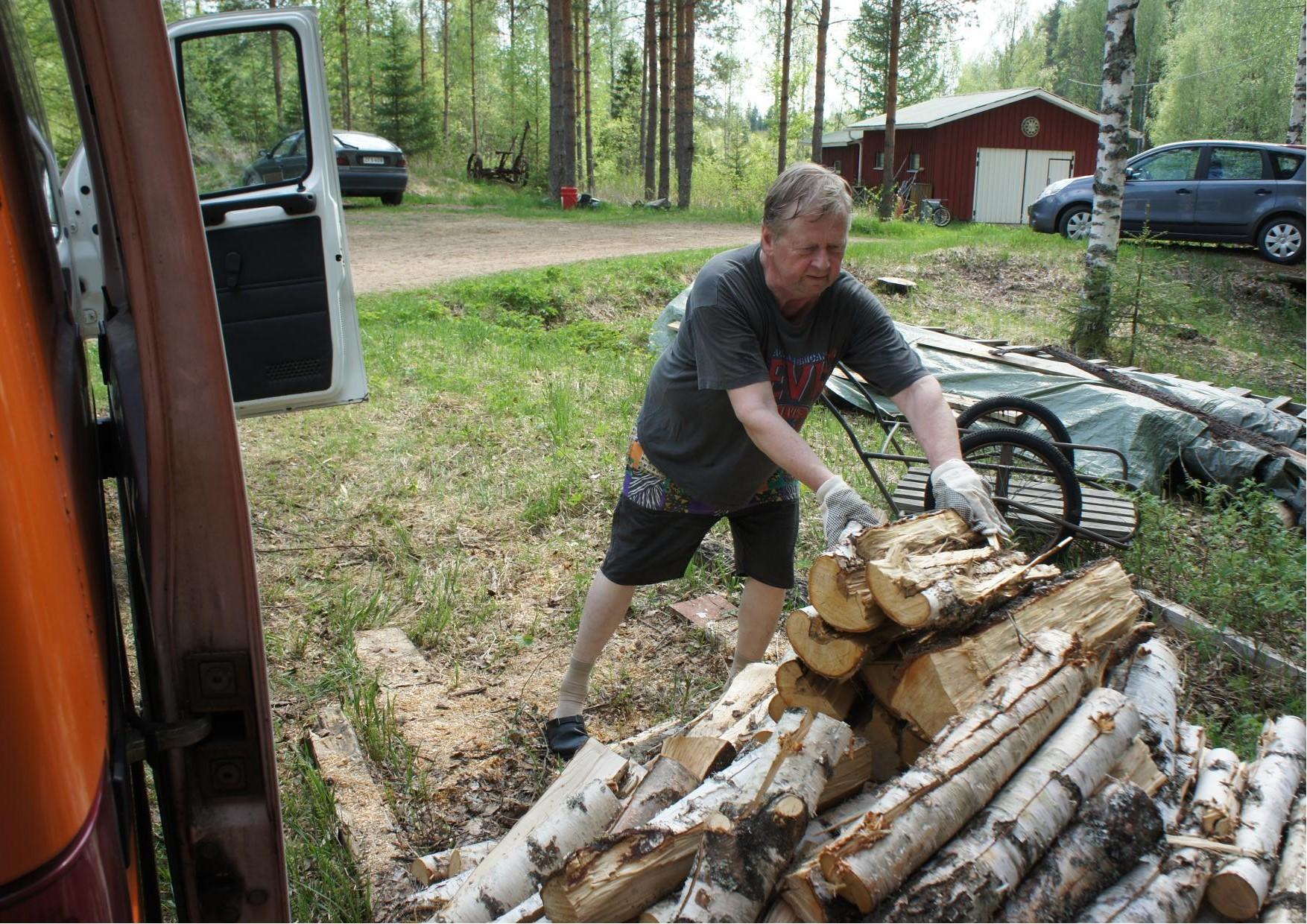 Muusikko Raimo Jokisalmi lastaa puuta, jotka toimitettiin hänen kotitilaltaan Kiuruveden makasiinille.