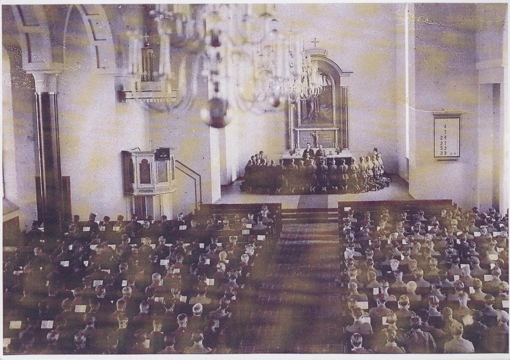 Arvi Simojoki ja Päivö Parviainen jakavat Kiuruveden kirkossa ehtoollista alokkaille, jotka kävivät rippikoulunsa asevelvollisuusaikana v. 1942.