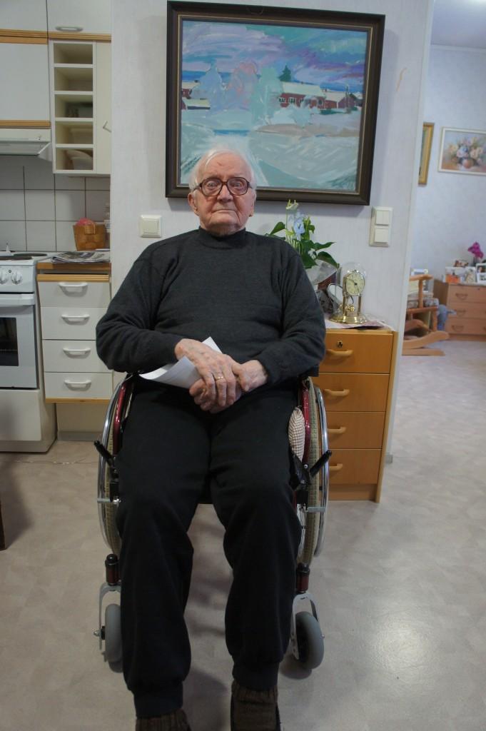 Kunnallisneuvos, arvostettu Rukajärven veteraani Paavo O. Saksman (24.1.1918 - 20.5.2015), kotonaan 24.1.2014. Taustalla maalaus kotitilasta.