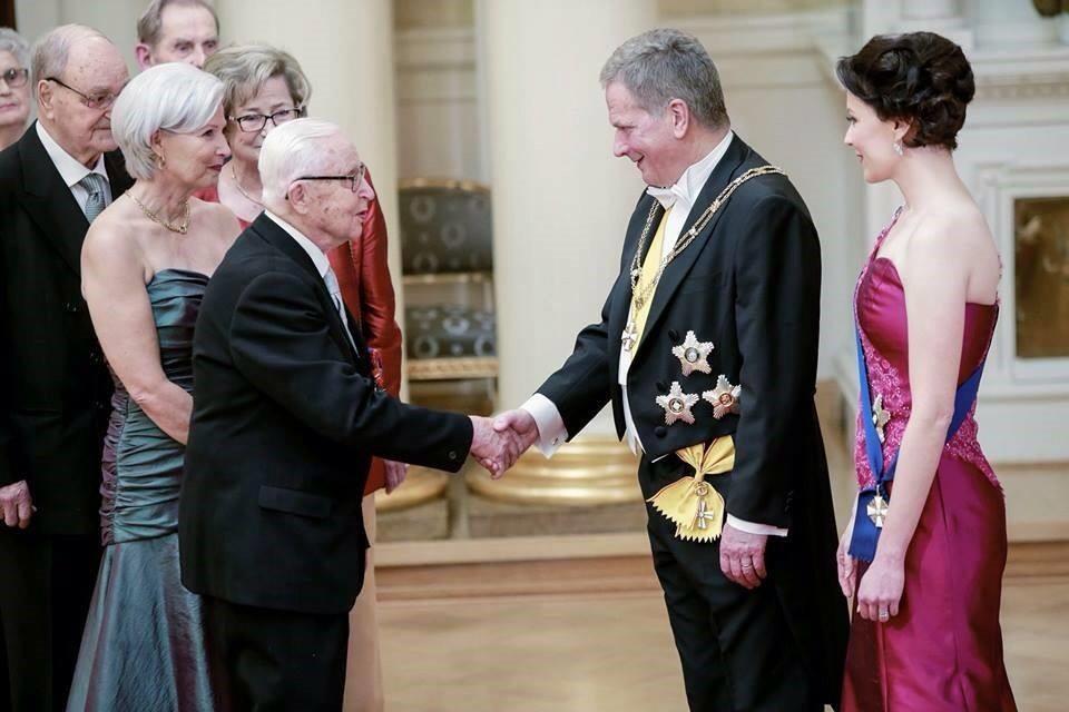 Sotaveteraani Ilmari Koppinen kättelemässä presidenttiä, hänen tyttärensä Anja Koppinen-Niemi. Professori Koppinen on Rukajärven suunnan historiayhdistyksen jäsen.