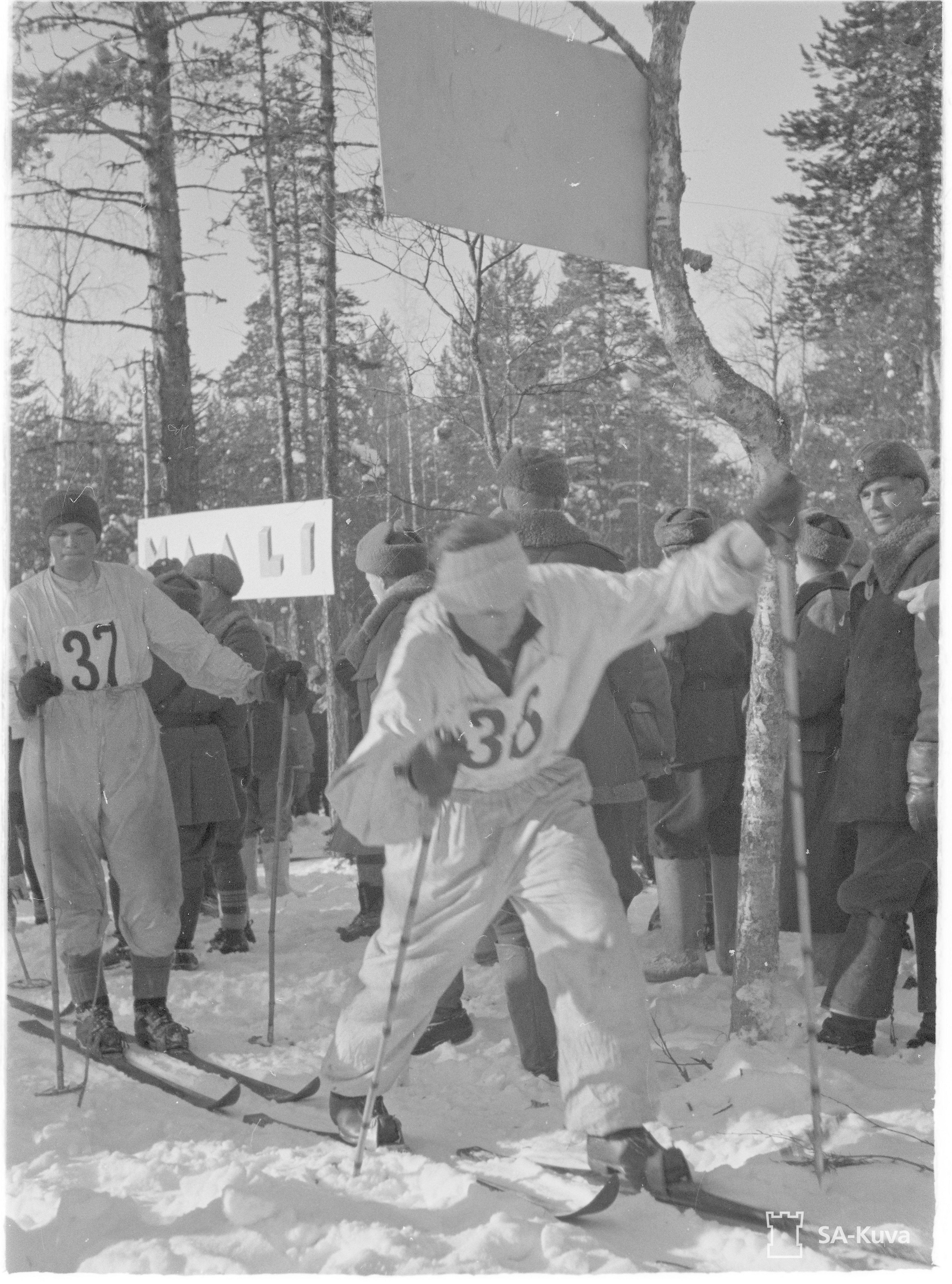 """""""Alikersantti Eino Hartikainen, 23-vuotias maanviljelijä Iisalmen maalaiskunnasta on noussut tällä sotaretkellä suurhiihtäjien eturiviin."""" SA-kuvateksti 28.2.1942."""